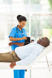 African nurse measuring blood pressure Stock Photo