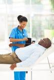 African nurse measuring blood pressure Stock Photo