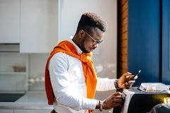 African office worker holding mobile phone and working with printer. Closeup side view portrait of african office worker holding mobile phone and working with Royalty Free Stock Images