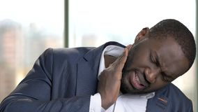 African office worker in suit suffering from toothache. Black man feels pain in his teeth indoor in the office, windows background stock video footage