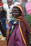 African Old Woman at Karatu Iraqw Market. Photo taken at Karatu, Tanzania on October 7, 2015. / Portrait of an unidentified African old woman on colourful Royalty Free Stock Photography