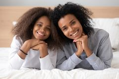 African older younger sisters lying on bed posing for camera royalty free stock photo