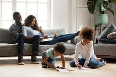 African parents relaxing on sofa while kids playing together dra. Black family relaxing at modern home, african american parents resting on sofa with laptop royalty free stock image
