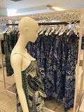 African Pattern Dress. African print summer dresses, hanging on a clothes rack and worn by a shop mannequin, on display in an up-market clothing shop or store stock images