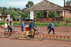 African peasants transported cargo on road bikes. Stock Image