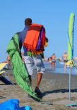 African peddler of fabrics and towels on the beach in summer Royalty Free Stock Photos