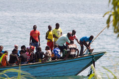 African people in boat lift the anchor. MPULUNGU, ZAMBIA - JUNE 6, 2014: Unidentified people sit in a boat, one unidentified man lift the anchor befor departure Royalty Free Stock Photo