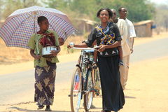 African people in the street zambia. Zambian people walking in the street in the small village mfuwe, one woman with a bicycle. You do not see a bicycle very Stock Photography