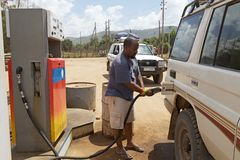 African petrol station. Cars at the african petrol station of the National Oil Company Ethiopia. The driver is filling the tank with the petrol pump Stock Image