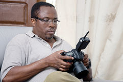 African photographer looking at the screen of his digital camera. After his photo shoot , this photographer looks at his pictures to appreciate Stock Photo