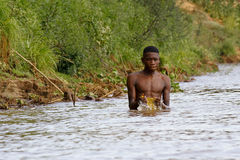 African poor man taking a bath in river Stock Image