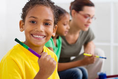 African preschooler. Portrait of a happy african preschooler holding paintbrush with classmate and teacher in background stock photos