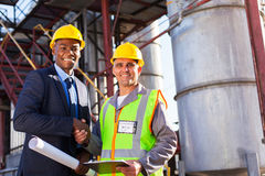 African refinery manager. Cheerful african refinery manager handshaking with senior worker in front of fuel-tanks Stock Photos