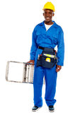 African repairman holding stepladder. With tool bag around his waist isolated against white background Royalty Free Stock Photos