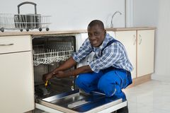 African Repairman Repairing Dishwasher Royalty Free Stock Image