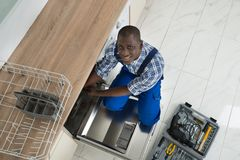 African Repairman Repairing Dishwasher Royalty Free Stock Images