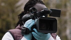 African reporter holding the camera with the latex gloves. Reporting about covid-19 outbreak