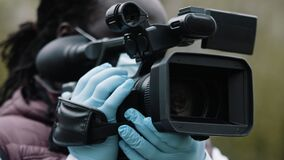African reporter with latex gloves holding the camera . Reporting about coronavirus pandemic
