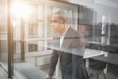 Young handsome guy with melancholy face is at office. African respectable man is behind the window optical fiber at office and looking into the distance. His Stock Images