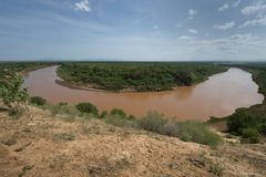 The African river Omo makes a horseshoe bend, the banks are covered with abundant greenery, the blue sky with few clouds, the sout. African river Omo makes a Royalty Free Stock Image