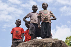 African Rural Children. Village boys in Africa pose on top of the rock in Uganda stock photo