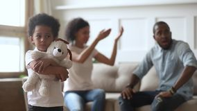 Unhappy little african son embraces toy while parents quarrelling. African sad little son feels afraid unhappy of parent fight, toddler kid holds embraces toy stock footage