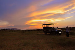 African safari Sunset. Jeep silhouetted against a magnificent African sunset close to Kruger Park Stock Photos
