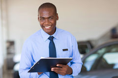 African salesman showroom. Handsome african salesman working at vehicle showroom royalty free stock photography