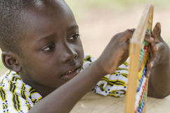 African school boy learning to count. Little african boy counting on abacus frame on blurred background Stock Photography