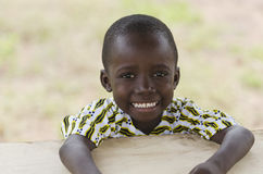 African school boy posing in his desk. Little african boy sitting at wooden table and smiling at camera with blurred background Stock Photography