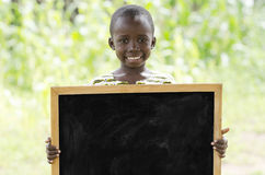 African school boy posing under the sun with a big blackboard copy space. Boy standing and holding signboard and looking at camera in front of building Royalty Free Stock Photos