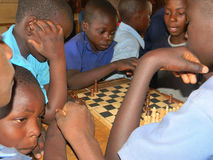 African school children playing chess. Norton,Zimbabwe 8August 2015. A group of African school children playing chesss inside a classroom at school.Chess is stock photos