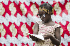 African school girl with big black glasses reading a book with blurred background. Young african girl with traditional accessories in hair reading book Stock Photos