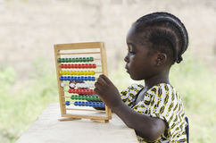 African school girl learning to count outdoors. Little african girl counting on abacus frame on blurred background Royalty Free Stock Photography