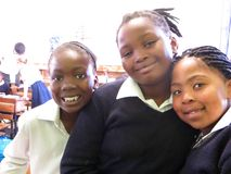 African School Girls. Close up of three young township girls smile in their class within a low income  school in Cape Town, South Africa Royalty Free Stock Images