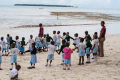 African school kids outdoor with teachers. Different African kids with their teacher on a beach in Tanzania. Shot was taken at Mikadi Beach, Dar Es Salaam in Stock Photography