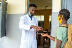 School teacher dispensing hand sanitizer for a school child
