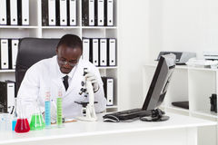 African scientist. African american medical scientist wearing lab coat with microscope and test tubes in laboratory Stock Images