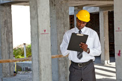 African site inspector surveying construction site. African man inspecting  a building site wearing a hard hat Royalty Free Stock Photography