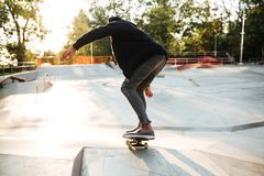 African skateboarder skating on a concrete skateboarding ramp Stock Images