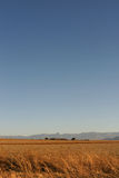 African skyline. Traditional African housing on the skyline with fields in the foreground and a mountain range in the background, and a big sky Stock Photo