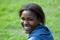 African smile. A beautiful African American black young woman head portrait with happy laughing expression in her pretty face showing her healthy white teeth Stock Photography