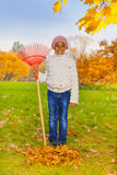 African smiling girl holds red rake during autumn Stock Photos
