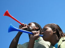African soccer fans with vuvuzela. African american young soccer fans blowing  vuvuzelas outside in front of a clear blue sky Stock Photography
