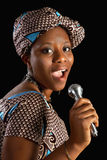 African song. Singing young Ghanese african woman against a black background Stock Photo