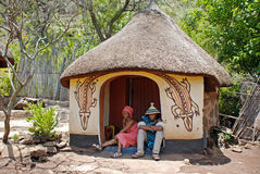 African Sotho couple in native tribal house. CULTURAL VILLAGE LESEDI, SOUTH AFRICA- JANUARY 1: African sotho couple wearing traditional handmade dress sitting Stock Photography