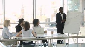 African speaker coach giving presentation on flipchart explaining financial graph. African american speaker coach giving presentation on flipchart explaining stock footage