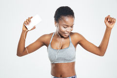 African sportswoman with mobile phone listening to music and dancing royalty free stock images