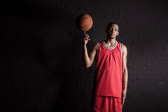 African sporty man holding basketball ball on finger. On black Royalty Free Stock Photography