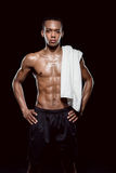 African sporty man with towel on shoulder on black Stock Photos